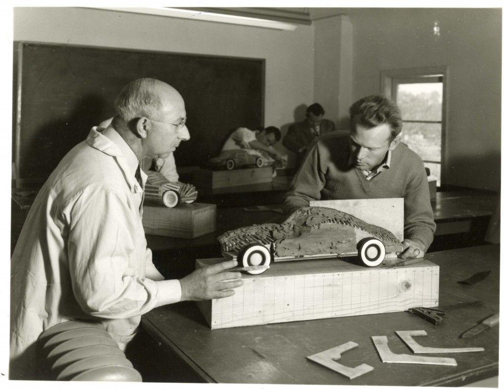 Joseph Thompson viewing a student's clay model of a car as the student works on the model, circa 1949. Art Center College of Design.