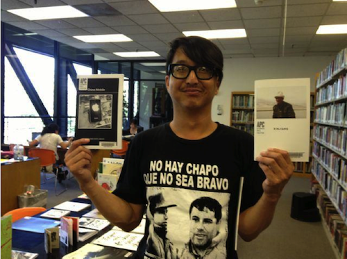 Student Linus Shentu with two photography zines he donated to the Library