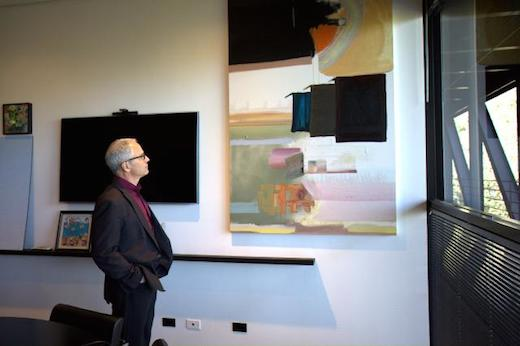 President Lorne M. Buchman admires student work by Tammy Chang (BFA 12) in his office.