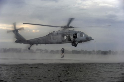 In this photo by Christopher Stoltz, members of Helicopter Sea Combat Squadron Seven (HSC-7) perform search and rescue jumps for qualification at Naval Station Norfolk in 2011.